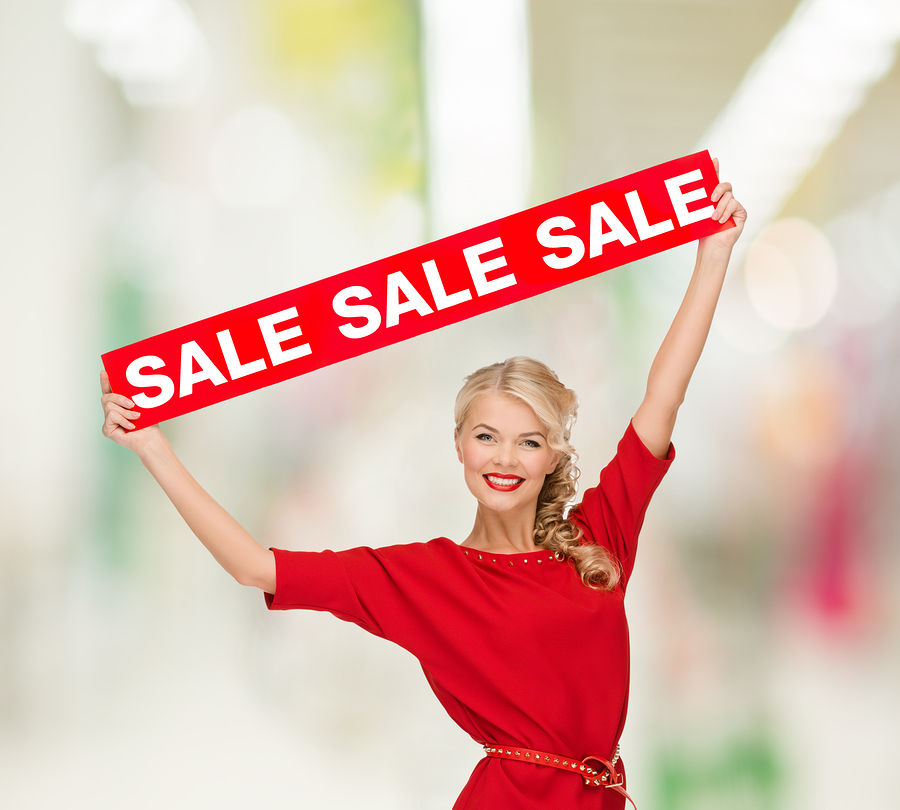 shopping, sale, christmas and mall concept - smiling woman in dress with red sale sign at shopping mall